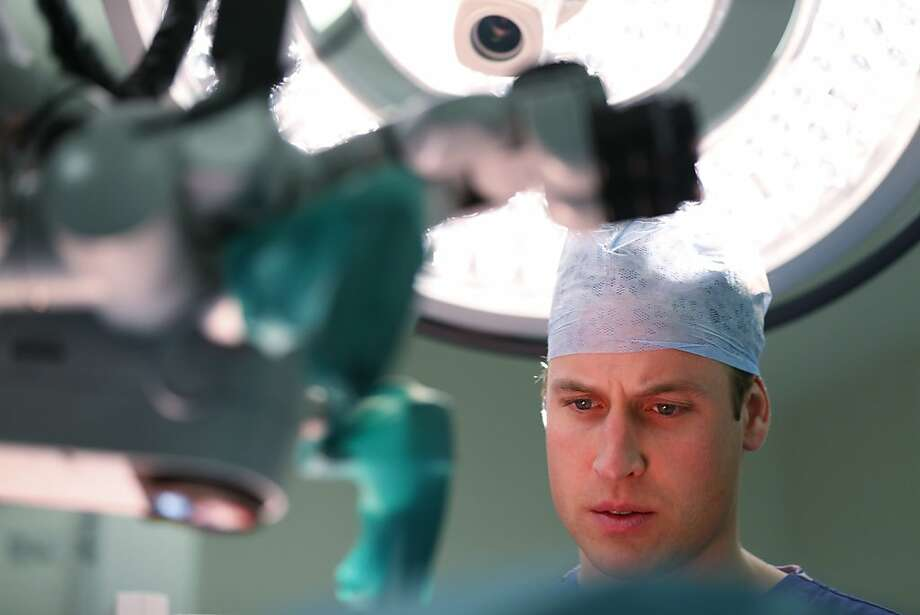 Mask on, Your Highness: Prince William observes a breast reconstruction operation during a visit to the Royal Marsden 