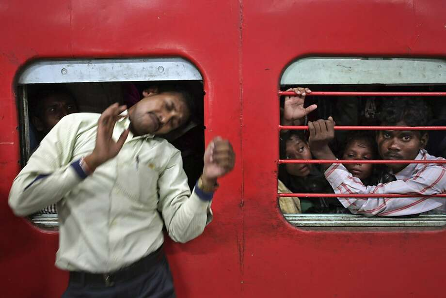 With cars packed like sardines,exiting a train in India can be an ordeal. This man climbed through an emergency window to get off at a station in New Delhi. The trains are especially crowded this time of year due to travelers going home for the Chhath Puja festival. Photo: Tsering Topgyal, Associated Press