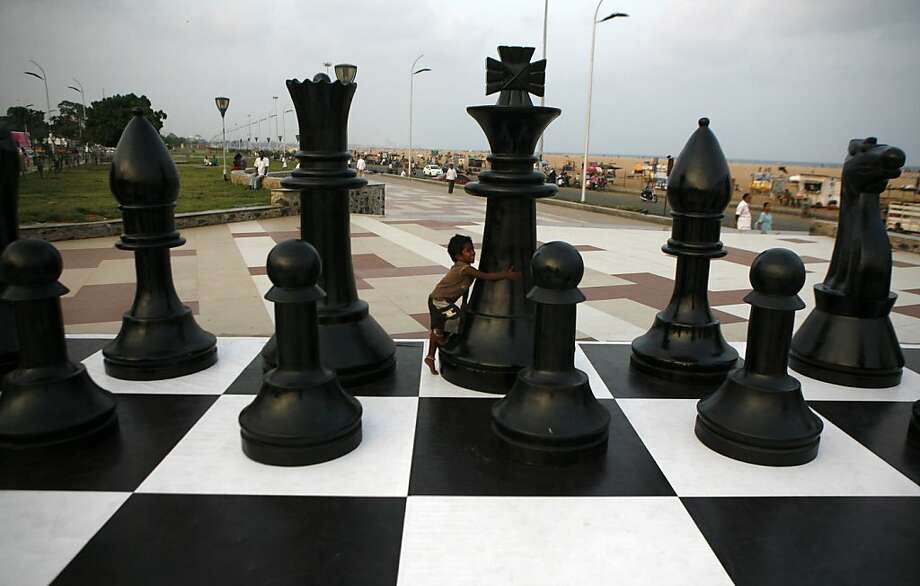 A quick examination of the chess board will tell you that this boy is unable to move his king because 1) it's surrounded by other pieces; and 2) it weighs about three times as much as he does. (Promotion for the FIDE World Chess Championship at Marina beach in Chennai, India.) Photo: Arun Sankar K, Associated Press