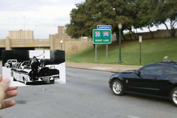 """In this photo by Ike Altgens of the Associated Press, juxtaposed with the current scene, Jackie Kennedy and Secret Service Agent Clint Hill climb on the back of the limousine after a fatal shot hit President John F. Kennedy, Tuesday, Sept. 10, 2013, in Dallas. Atgens was standing on Elm Street when he heard a blast that he recognized as gunfire and saw the President had been struck in the head. """"I had pre-focused, had my hand on the trigger, but when JFK's head exploded, sending substance in my direction, I virtually became paralyzed,"""" Altgens later told author Richard B. Trask. """"This was such a shock to me that I never did press the trigger on the camera."""" Seconds later Atgens recomposed himself and shot the picture being held in this photo. (Cody Duty / Houston Chronicle)"""