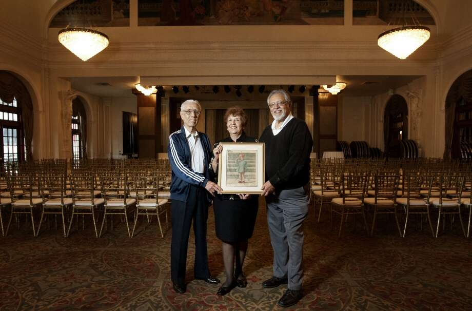 From left, Ernest Aguia, Tina Adame, center, Jim Montero, right, hold a framed, anniversary edition of the Houston Chronicle commemorating the death of President of John F. Kennedy at the Rice Hotel, Tuesday, Oct. 22, 2013, in Houston. The three were at the Rice Hotel when JFK spoke to the League of United Latin American Citizens in 1963 before he was hit with a fatal shot in Dallas the next day. (Cody Duty / Houston Chronicle) Photo: Cody Duty, Houston Chronicle