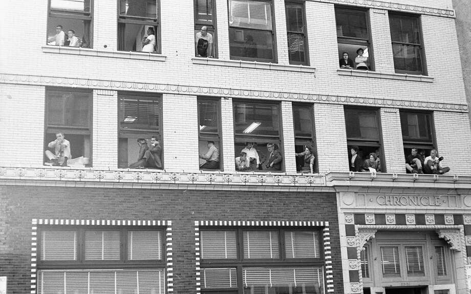 11/21/1963 - Houston Chronicle staffers look out the windows of the Houston Chronicle building to catch a glimpse of President John F Kennedy and his motorcade arriving at the Rice Hotel across the street. Photo: Houston Chronicle