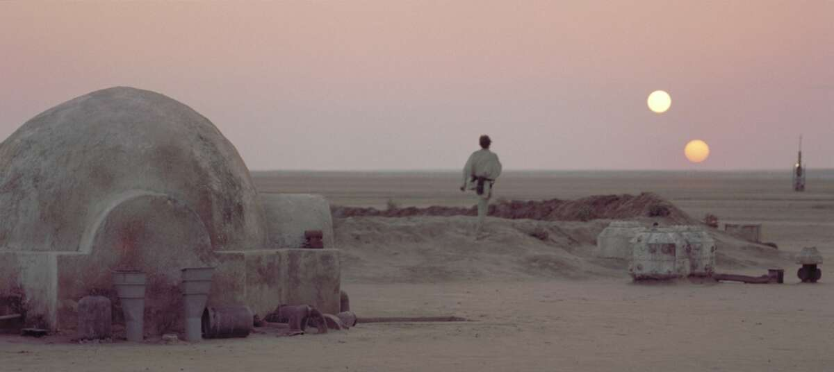 """After discussing his future plans with his Uncle Owen, Luke Skywalker leaves the Lars Homestead and heads towards the vista to watch the twin suns of Tatooine set while he reflects upon his destiny in a scene from the film """"Star Wars.""""."""