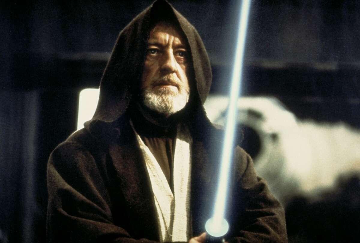 Ben (Obi-Wan) Kenobi (Alec Guinness) holds his lightsaber on the Death Star battle station in a scene from the film