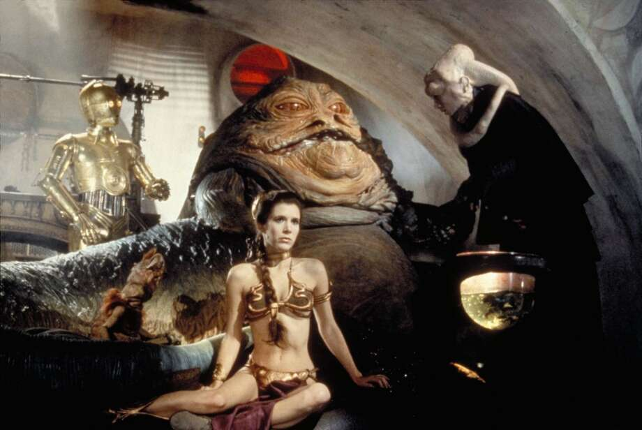 "Jabba the Hutt with Princess Leia (Carrie Fisher, foreground) in ""Return of the Jedi.""   Lucasfilm Ltd. & TM. All Rights Reserved. Photo: Courtesy Lucasfilm Ltd."