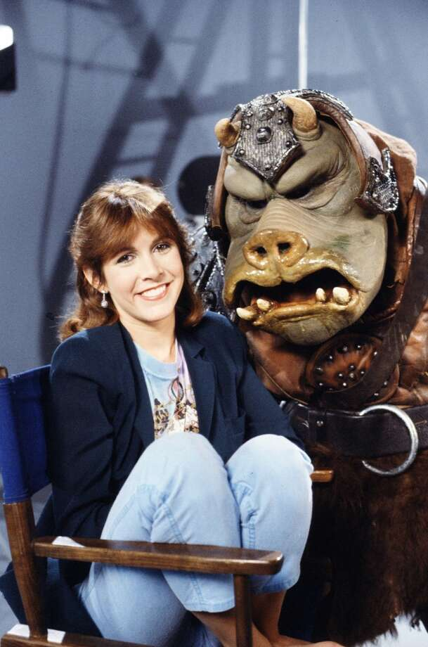 Promotional portrait of American actress Carrie Fisher as she poses with a Gamorrean guard on the set of 'Classic Creatures: Return of the Jedi' (directed by Robert Guenette), a documentary about the second film in the Star Wars saga that focuses on variety of unusual beings that populate the film's world; the program was originally broadcast on November 21, 1983. (Photo by CBS Photo Archive/Hulton Archive) Photo: Getty Images