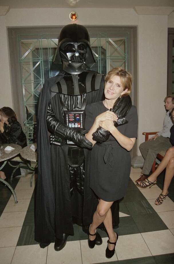 Actress Carrie Fisher with an actor in a Darth Vader costume at a 'Star Wars Extravaganza', held at Alexandra Palace in London, 12th October 1995. (Photo by Dave Benett/Getty Images) Photo: Getty Images