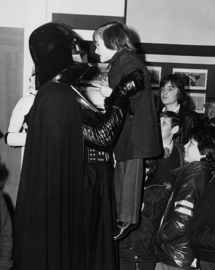 31st March 1980:  Eight year old Derek Moon from Scotland meeting Darth Vader during his visit to Selfridges in Oxford Steet to promote an exhibition of set models, original drawings and figures from 'The Empire Strikes Back'.  (Photo by David Levenson/Keystone/Getty Images) Photo: Getty Images