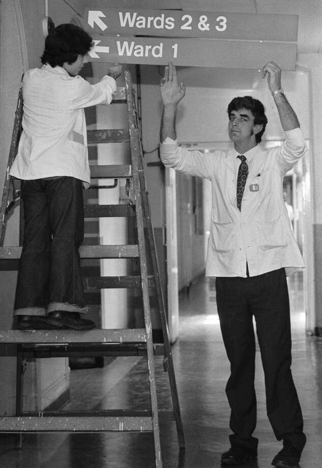 English actor Peter Mayhew (right) helps put up signs to the wards at King's College Hospital, where he works as an orderly, 3rd June 1977. Mayhew, who is 7'3'' tall, gained fame as the Wookiee Chewbacca in George Lucas' 'Star Wars' films. (Photo by Colin Davey/Evening Standard/Hulton Archive/Getty Images) Photo: Getty Images