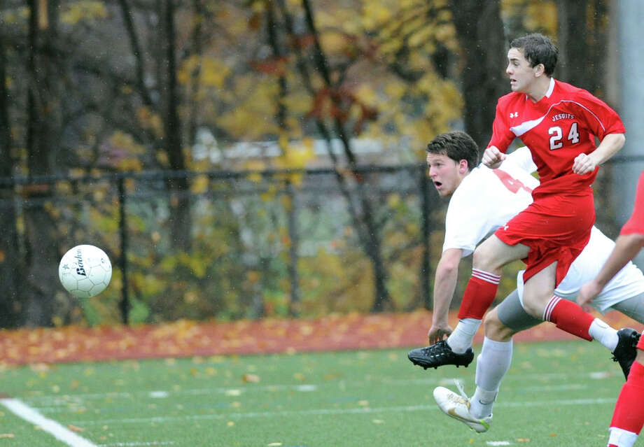 Will Gittings (# 4) of Greenwich watches as the ball he headed sails into the net for his second of the three goals during the Class LL boys soccer playoff game between Greenwich High School and Fairfield Prep at Greenwich, Thursday, Nov. 7, 2013. At right looking on is Fairfield Prep's Aiden Rooney (# 24). Greenwich advanced with a 4-0 win over Fairfield Prep. Photo: Bob Luckey / Greenwich Time