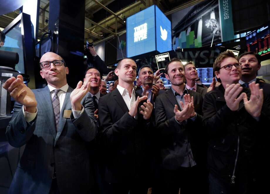 Twitter CEO Dick Costolo, Chairman and co-founder Jack Dorsey, and co-founders Evan Williams and Biz Stone, front row left to right, applaud as they watch the the New York Stock Exchange opening bell rung, Thursday, Nov. 7, 2013.  If Twitter's bankers and executives were hoping for a surge on the day of the stock's public debut, they got it. The stock opened at $45.10 a share on its first day of trading, 73 percent above its initial offering price.  (AP Photo/Richard Drew) ORG XMIT: NYRD108 Photo: Richard Drew / AP