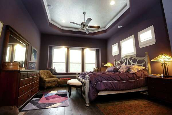 The master bedroom features silver accents on the ceiling that coordinate with the headboard.