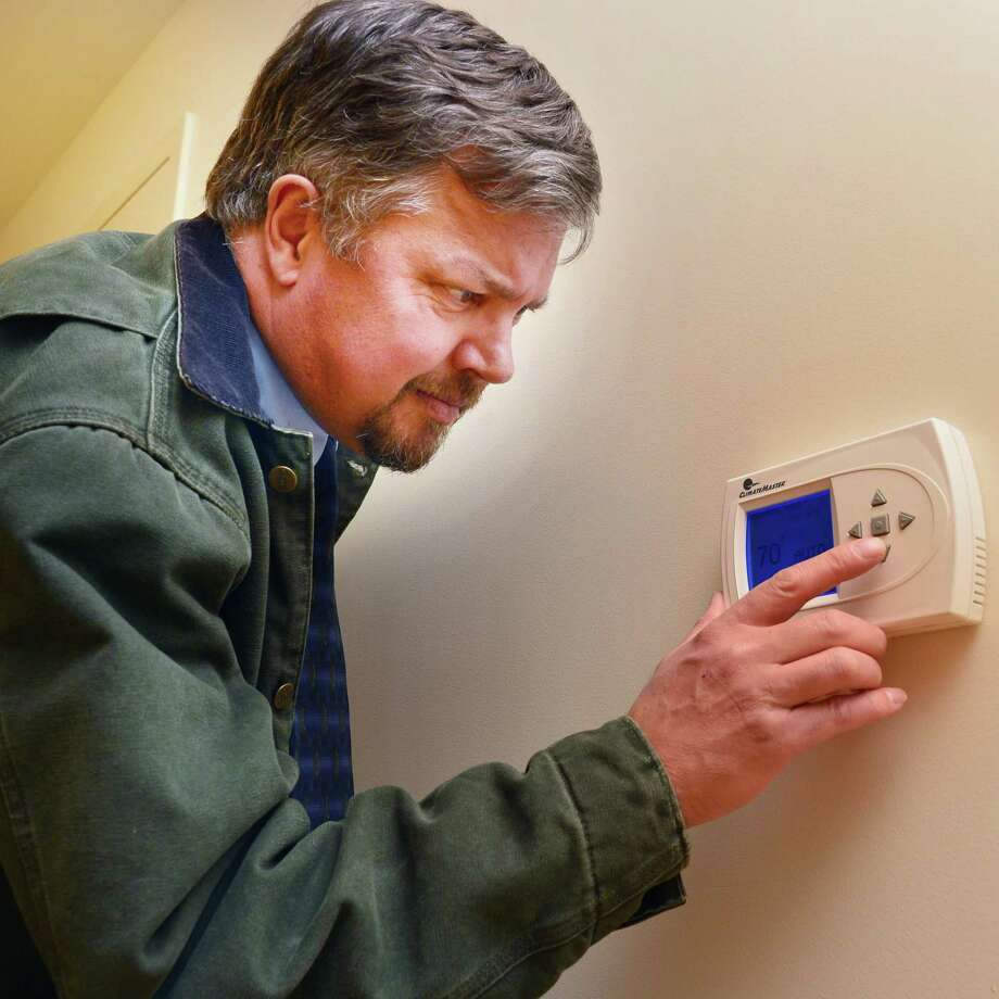 Senior project manager T. Scott Hawkins of Sano-Rubin Construction services check the thermostat in a newly renovated apartment at the environmental and energy efficiently upgraded Monument Square Apartments Thursday Nov. 7, 2013, in Troy, NY.  (John Carl D'Annibale / Times Union) Photo: John Carl D'Annibale / 00024550A