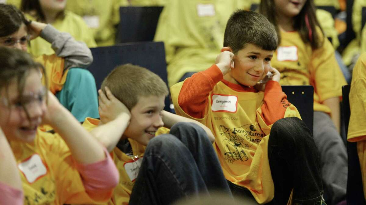 Timothy Shelly, second from left and Benjamin Chick, right of Veeder Elementary School react to a loud sound during a magic versus science show at the 25th anniversary of Science Day Thursday Nov. 7, 2013. at the GE Global Research center in Niskayuna, N.Y. Moore showed students from around the capital region about chemical reactions in comparison to magic reactions. (Skip Dickstein / Times Union)