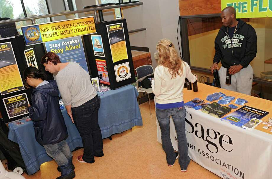 Alumnus Malachi Jackson of Schenectady, right, hands out free items such as coffee mugs at a display set up in the campus center at Sage College of Albany for Drowsy Driving Awareness Day  Thursday, Nov. 7, 2013 in Albany, N.Y.  The New York State Partnership Against Drowsy Driving (NYPDD) and the Sage Alumni Association organized the event. (Lori Van Buren / Times Union) Photo: Lori Van Buren / 00024556A