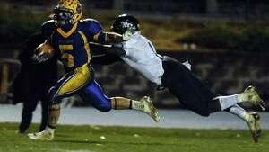 Seymour's Joseph Salemme scores a touchdown as Ansonia's Jaiquan McKnight tries to catch him Thursday, Nov. 7, 2013 during their football game at Seymour High School in Seymour, Conn.