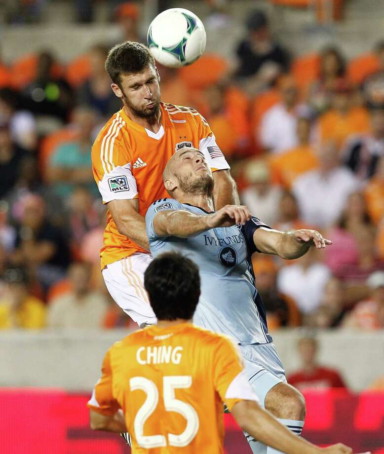 The Dynamo's Will Bruin, top, challenges Sporting KC's Aurelien Collin in Sporting's 1-0 win May 12. Photo: Bob Levey, Freelance / ©2013 Bob Levey