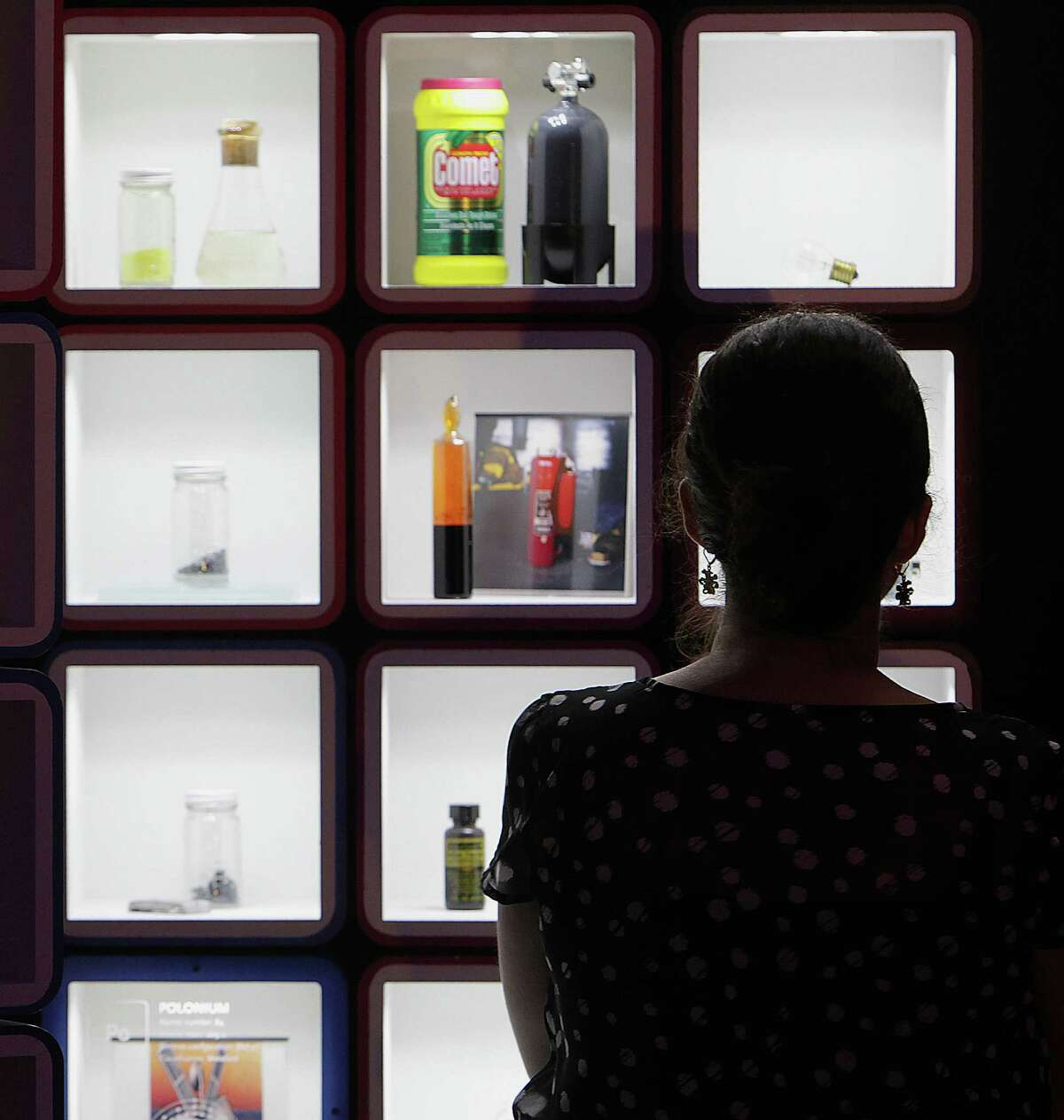 Eydie Rojas looks over her work while completing the periodic table blocks for the museum's latest interactive exhibit.