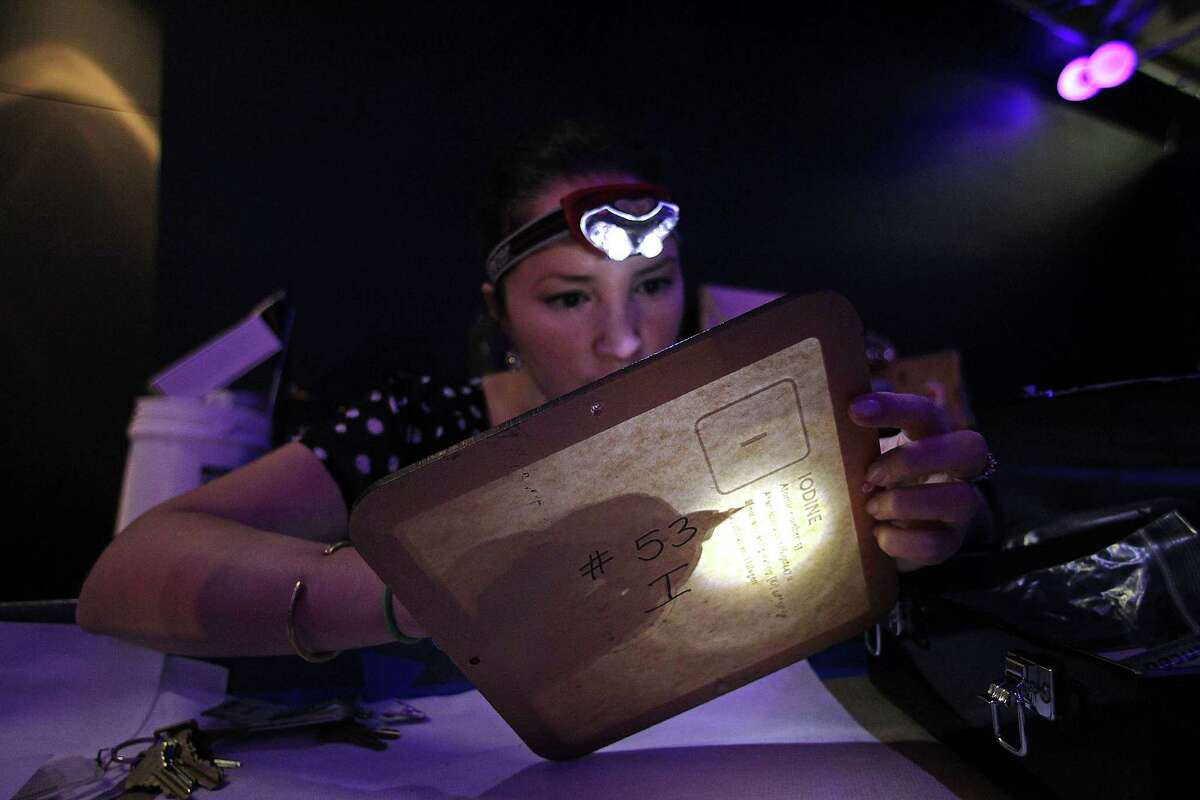 Eydie Rojas removes a protective covering from a tempered glass panel for the periodic table during the renovation of the Welch Hall of Chemistry at the Houston Museum of Natural Science on Wednesday.