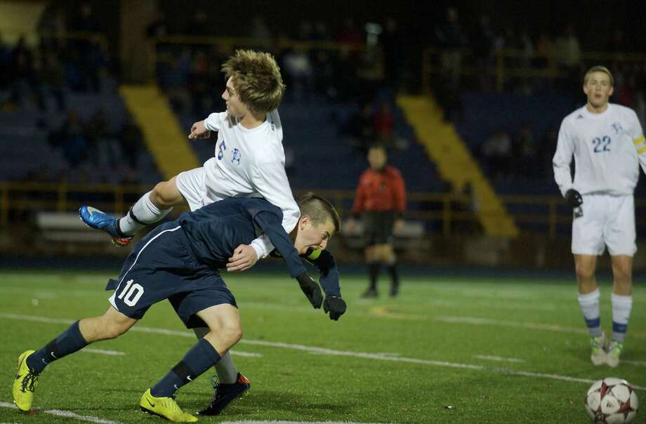 Newtown's Brenton Scott, 5, and Staple's Jose Alanis, 10, get tangled up during a Connecticut high school Class LL boys soccer game between Staples and Newtown high schools in Newtown, Conn on Thursday night, November 7, 2013. Photo: H John Voorhees III / The News-Times Freelance