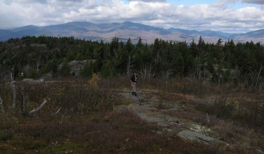 Photo by Herb Terns. A bushwhacker makes his way up the final steps of Hail Mountain. The Adirondack High  Peaks are in the background. Photo: Picasa