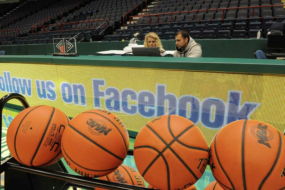 Siena senior Nicole Heck of Amsterdam, left, gets instruction on how to work the LCD displays for the timer and scoreboard from a computer with Mike Magaletta of ANC Sports at the Times Union Center on Wednesday, Nov. 6, 2013 in Albany, N.Y. The two were setting up for the big basketball matchup between Siena and UAlbany Friday night.  (Lori Van Buren / Times Union) Photo: Lori Van Buren