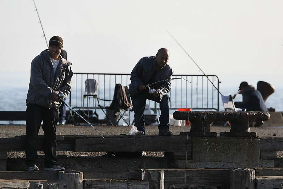 Martin Ngo (left) brings his friend for a first time fishing on the pier at Crissy Field during the federal government shutdown in San Francisco, California, on Tuesday, October 1, 2013.  Martin usually comes to fish once a week. Photo: Liz Hafalia, The Chronicle