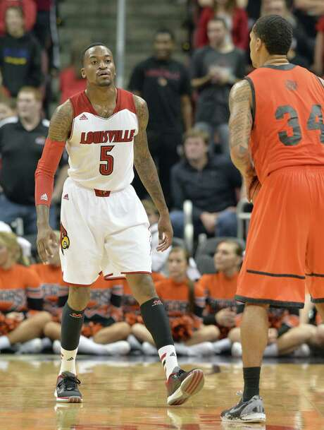 Louisville's Kevin Ware (left) played his first game Wednesday since breaking his right leg in March. Photo: Timothy D. Easley / Associated Press