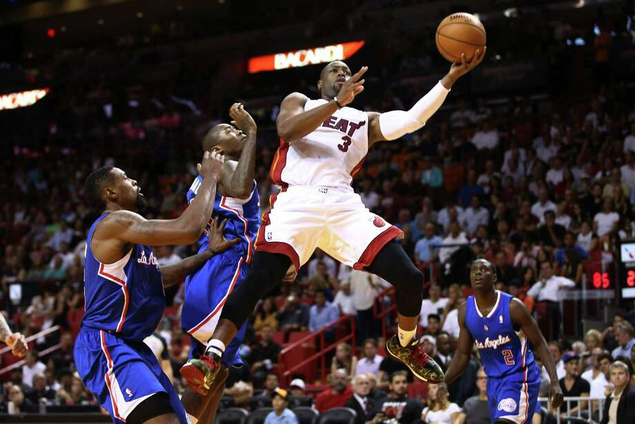 Miami Heat's Dwyane Wade (3) drives between Los Angeles Clippers players DeAndre Jordan, left, Jamal Crawford, second from left, and Darren Collison (2) for two points during the first half of an NBA basketball game in Miami, Thursday, Nov. 7, 2013. (AP Photo/J Pat Carter) ORG XMIT: FLJC107 Photo: J Pat Carter / AP