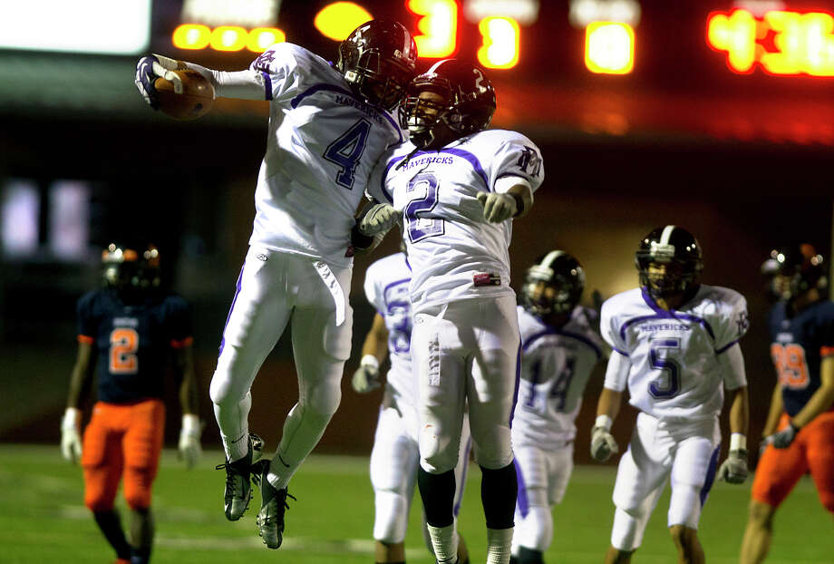 Morton Ranch's Jordon Ramirez, left, celebrates with Avery Ross, right, after he intercepted a pass intended for Seven Lakes Cameron Thomas during the second quarter at Rhodes Stadium, Thursday, Nov. 7, 2013, in Katy. Morton Ranch scored on the following drive. Photo: Cody Duty, Houston Chronicle / © 2013 Houston Chronicle