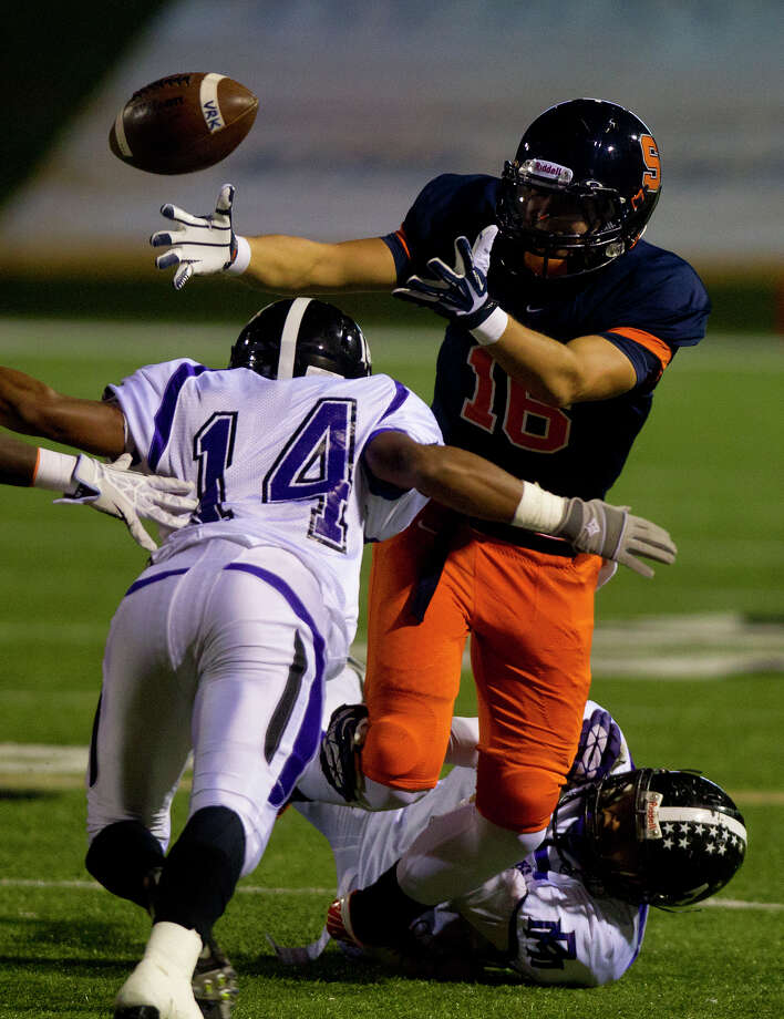 Seven Lakes Sid Turnbull can't make the catch as he's brought down by Morton Ranch's Colton Hughes, left, and Jordon Ramirez, right, during the third quarter at Rhodes Stadium, Thursday, Nov. 7, 2013, in Katy. Morton Ranch won 28-17. Photo: Cody Duty, Houston Chronicle / © 2013 Houston Chronicle