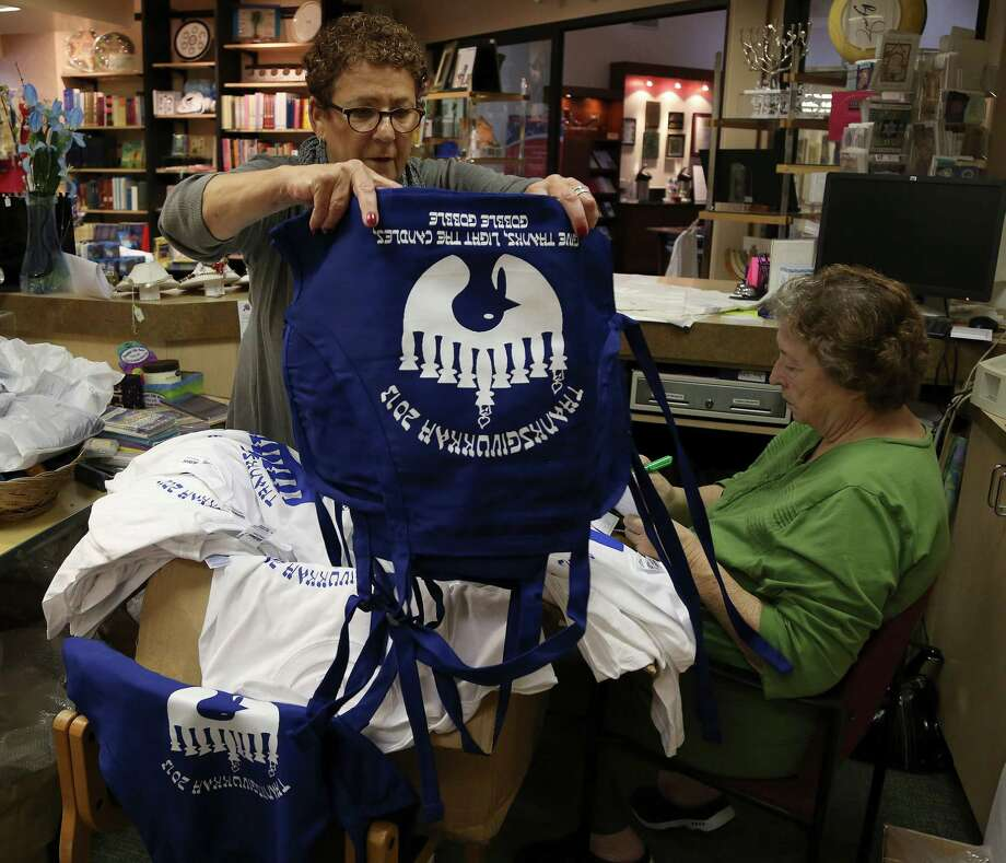 Sylvia Brody, left, volunteer buyer for the Sisterhood gift shop inside the Congregation Emanu El and Betty Rosenthal, right, volunteer gift store manager, work on filling orders for their Thanksgivukkah t-shirts and aprons at the Congregation Emanu El, Wednesday, Oct. 30, 2013, in Houston. Thanksgivukkah, is the holiday that marks the combination of Thanksgiving and Hannukah, that happens this year.  ( Karen Warren / Houston Chronicle ) Photo: Karen Warren, Staff / © 2013 Houston Chronicle