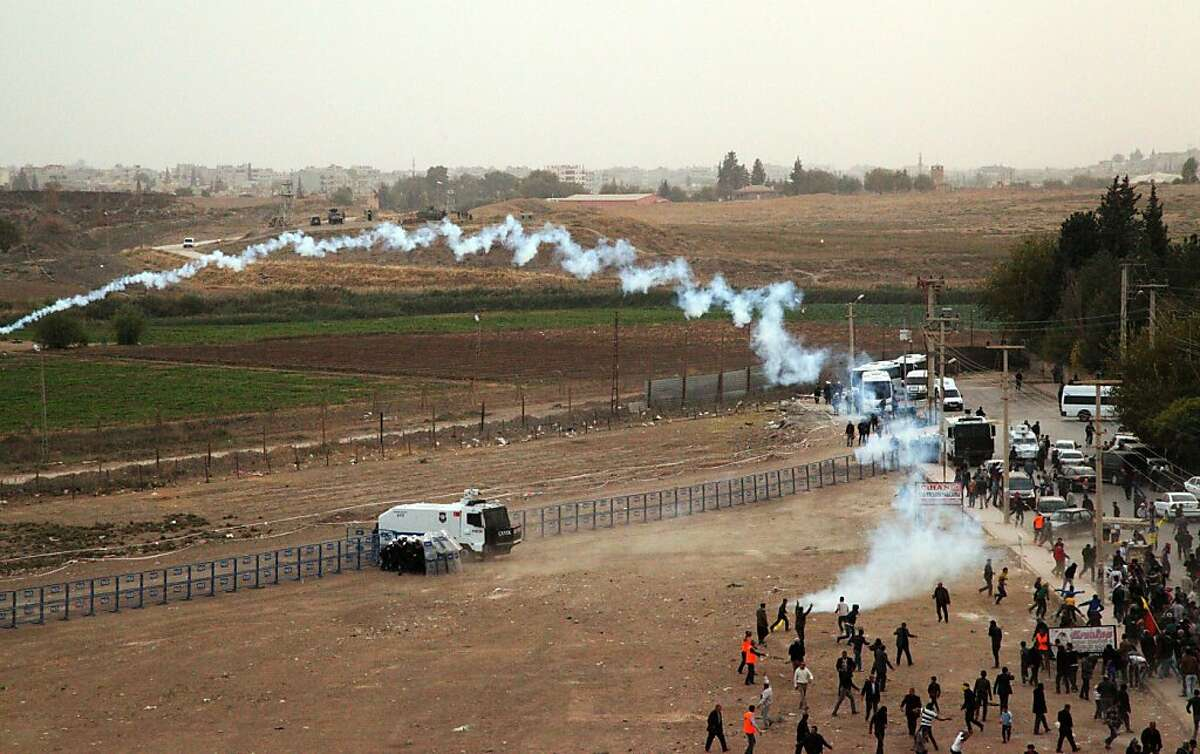 Turkish riot police use tear gas to disperse Turkish-Kurd protesters demonstrating on the Turkish side as Syrian Kurds gather on the other side of the border in Mardin's Nusaybin district on November 7, 2013. Kurdish people protest against the construction by the Turkish government of a 2.5-kilometer-long wall along the border between Turkey and Syria. TOPSHOTS/AFP PHOTOSTR/AFP/Getty Images