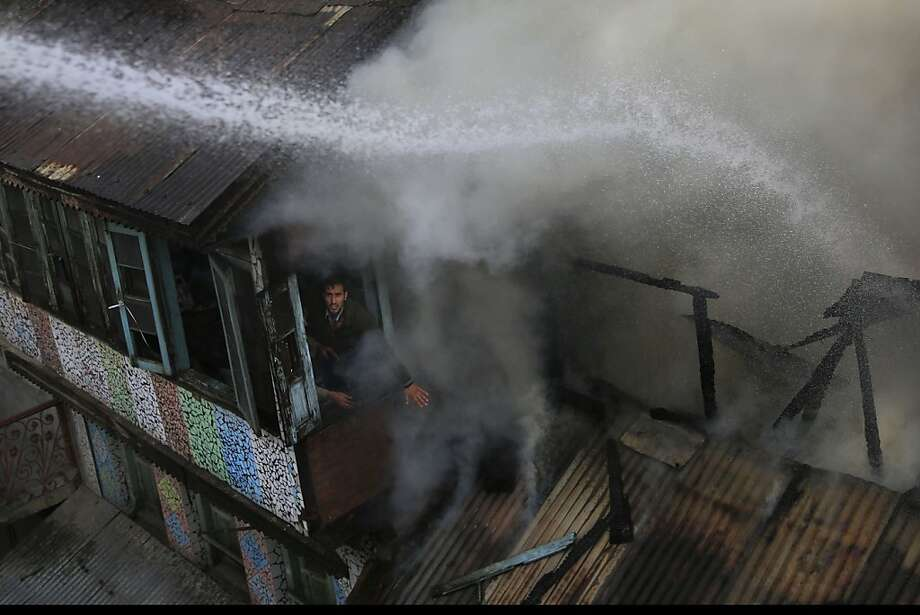 A Kashmiri man gestures to firefighters to spray water while extinguishing a fire in Srinagar, India, Thursday, Nov. 7, 2013. At least three buildings housing dozens of warehouses in a busy shopping area of Srinagar where damaged by the fire Thursday. Winter in Indian Kashmir brings not only freezing cold and snow, but also widespread incidents of fire blamed mainly on accidental ignition of charcoal, usually stored for fighting cold and cooking purposes on the top floors of Kashmiri homes. (AP Photo/Dar Yasin) Photo: Dar Yasin, Associated Press