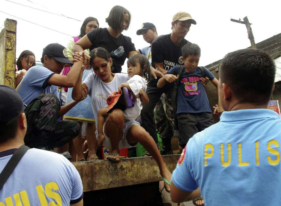 Residents living near the slopes of Mayon volcano are evacuated to public schools Thursday by police in anticipation of the powerful typhoon Haiyan that threatened the central Philippines. Photo: Nelson Salting / Associated Press