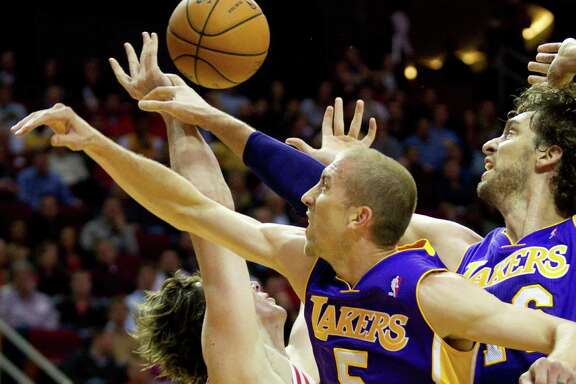 Lakers guard Steve Blake (5) and center Pau Gasol separate Rockets center Omer Asik from the ball during the first half of Los Angeles' win Thursday night at Toyota Center.