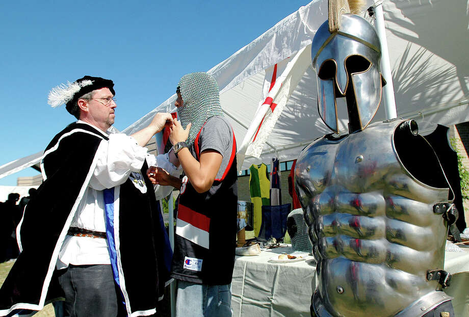Chris DeSmith, left, helps T.J. Omoso try on a chainmail coif, which was a type of armor used to protect the head during a battle in the medieval times, Tuesday, Nov. 21, 2006, during the 12th annual Sci Tech Renaissance Festival at The Science Academy of South Texas in Mercedes, Texas. The Sci Tech senior class sponsored the event that recreates the world of the 16th Century. (AP Photo/The Valley Morning Star, Gabe Hernandez) Photo: GABE HERNANDEZ, File Photo / THE VALLEY MORNING STAR