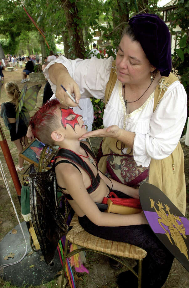 A young warrior readys for battle with the help of face painter Debbie Bullock at the Texas Renaissance Festival. Photo: Orvis Melvin, File Photo / 2002 Texas Renaissance Festival