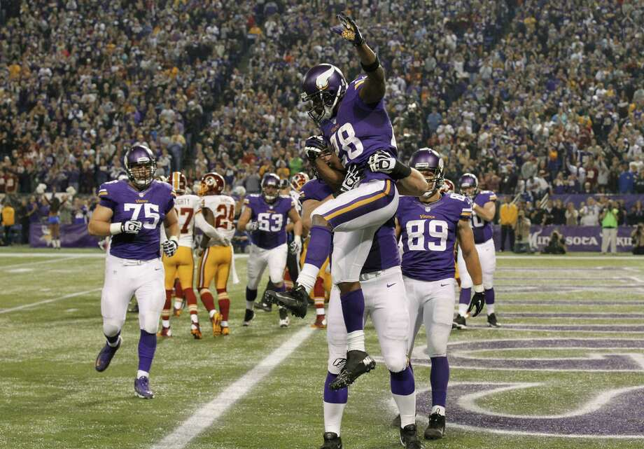 Vikings running back Adrian Peterson is lifted by teammates after scoring on a 1-yard run during the second half in Minneapolis. Peterson scored twice Thursday. Photo: Ann Heisenfelt / Associated Press