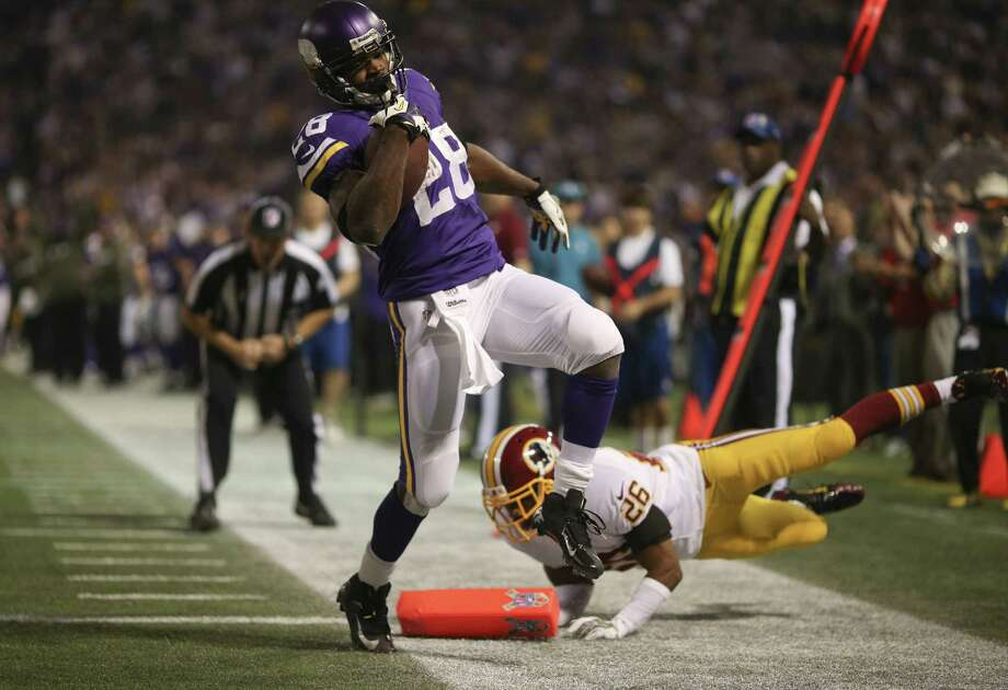 Vikings running back Adrian Peterson (28) makes his way past the Redskins' Josh Wilson to finish an 18-yard TD run in the first quarter Thursday night. Photo: Jeff Wheeler, MBR / Minneapolis Star Tribune