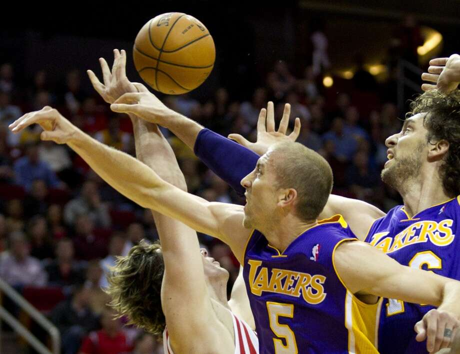 Lakers point guard Steve Blake (5) and Lakers center Pau Gasol (16) knock the ball away from Rockets center Omer Asik (3). Photo: Brett Coomer, Houston Chronicle