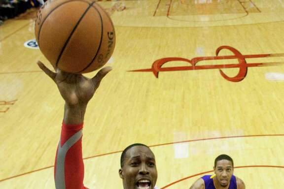 Rockets center Dwight Howard shoots over Lakers counterpart Jordan Hill on Thursday night. Howard made half of his 10 field-goal tries but was just 5-of-16 from the free-throw line.
