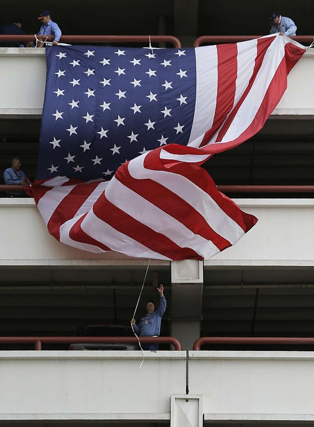 In preparation for Veteran's Day, workers hang a three-story long U.S. Flag off a parking garage, Thursday, Nov. 7, 2013, in downtown San Antonio. Veteran's Day is Monday. (AP Photo/Eric Gay)