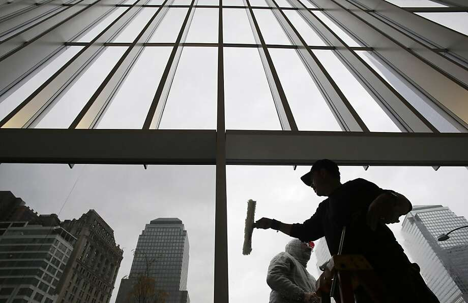 Workers clean the glass windows at the lobby of 4 World Trade Center, Thursday, Nov. 7, 2013, in New York.  The 1,776-foot One World Trade Center is the marquee skyscraper at ground zero; but the first office tower to open there will be its shorter neighbor 4 World Trade Center on Wednesday, Nov. 13. (AP Photo/Mark Lennihan) Photo: Mark Lennihan, Associated Press