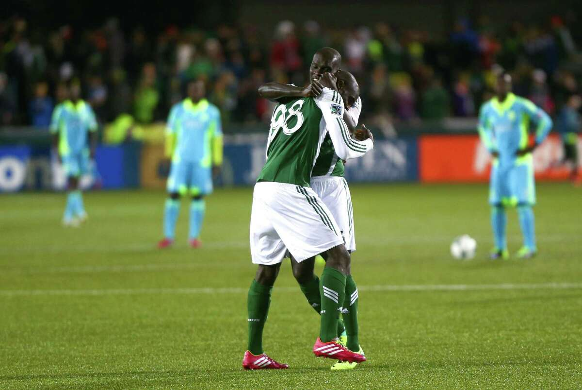 Portland Timbers players Mamadou Danso (98) and Pa-Modou Kah (44) celebrate after a goal in the second half during an MLS Playoff match at JELD-WEN Field in Portland on Thursday, November 7, 2013. The Timbers defeated the Sounders, ending the season for Seattle.