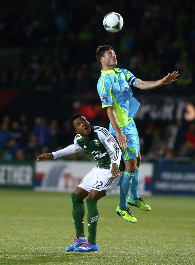 Seattle Sounders player Brad Evans heads a ball over Portland Timbers player Rodney Wallace during an MLS Playoff match at JELD-WEN Field in Portland on Thursday, November 7, 2013. The Timbers defeated the Sounders, ending the season for Seattle. Photo: JOSHUA TRUJILLO, SEATTLEPI.COM / SEATTLEPI.COM