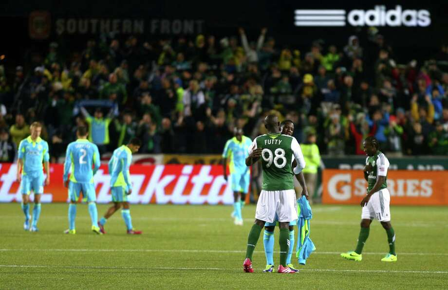 Portland Timbers player Mamadou Danso hugs Sounders player Eddie Johnson after the Timbers defeated the Sounders during an MLS Playoff match at JELD-WEN Field in Portland on Thursday, November 7, 2013. The Timbers defeated the Sounders, ending the season for Seattle. Photo: JOSHUA TRUJILLO, SEATTLEPI.COM / SEATTLEPI.COM