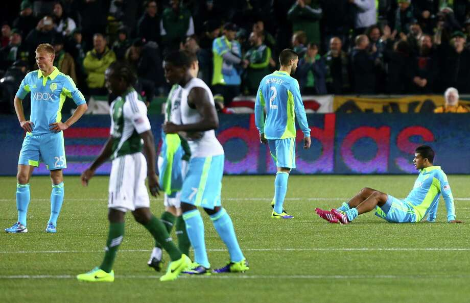 Dejected Seattle Sounders players, from left, Andy Rose (25), Clint Dempsey (2), and DeAndre Yedlin (17) react as the clock winds down against the Portland Timbers during an MLS Playoff match at JELD-WEN Field in Portland on Thursday, November 7, 2013. The Timbers defeated the Sounders, ending the season for Seattle. Photo: JOSHUA TRUJILLO, SEATTLEPI.COM / SEATTLEPI.COM