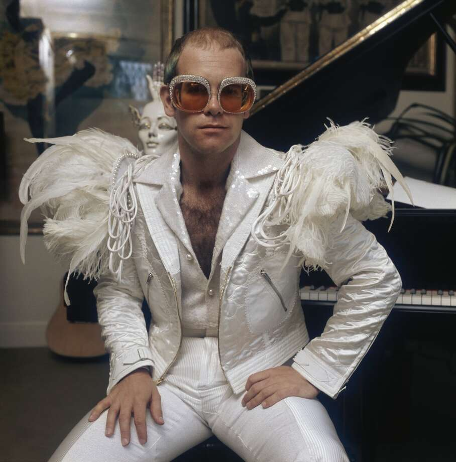 English pop singer Elton John in a flamboyant stage outfit of white suit with feather trim and rhinestone encrusted glasses, circa 1973. (Photo by Terry O'Neill/Hulton Archive/Getty Images) Photo: Terry O'Neill, Getty Images