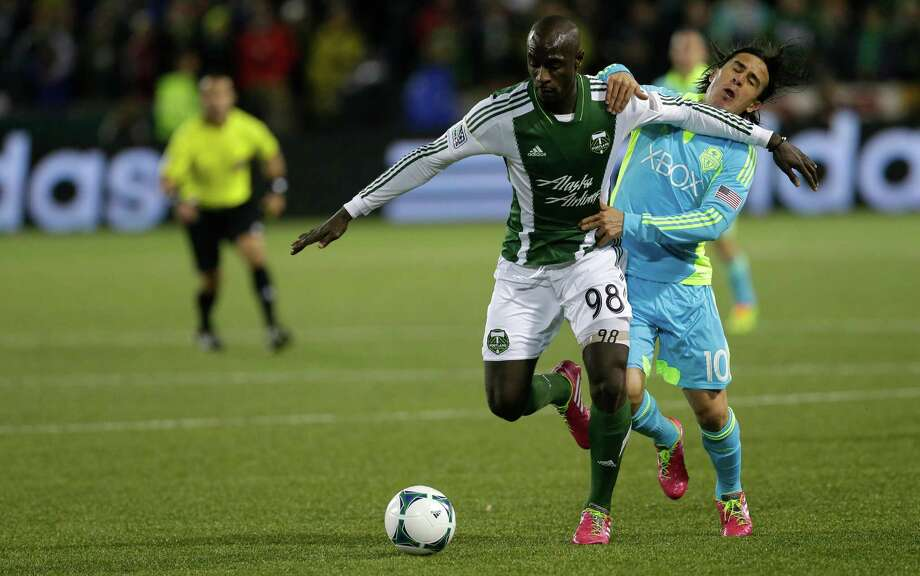 Portland Timbers' Mamadou Danso, left, pushes off Seattle Sounders' Mauro Rosales in the second half of the second game of the Western Conference semifinals in the MLS Cup soccer playoffs, Thursday, Nov. 7, 2013, in Portland, Ore. Photo: Ted S. Warren, AP / AP